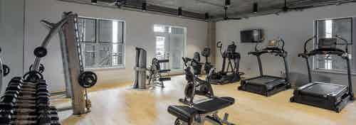 AMLI Downtown fitness center with free weights rack and cardio machines on a light wooden floor with concrete ceiling above