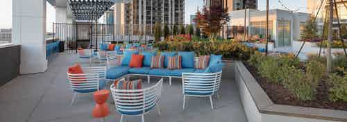 AMLI Arts Center rooftop with blue outdoor seating and orange pillows near raised green plants with city view in background