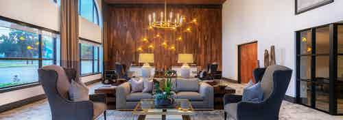 AMLI Grapevine clubroom with plush gray lounge seating and golden chandeliers and large windows and hardwood accent wall