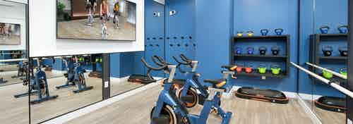 Interior of fitness center at AMLI Decatur with fitness on demand on large screen TV with spin bikes and kettle bells