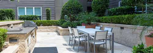 Daytime view of outdoor dining and grilling area at AMLI River Oaks apartment building with lush greenery and potted flowers