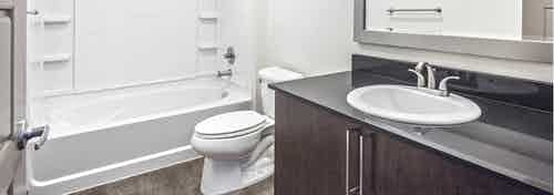 Interior view of an AMLI Mark24 apartment bathroom with white walls black quartz counter top and large shower tub combination
