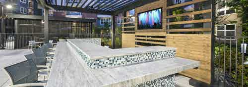Evening view of AMLI Decatur open layout pool bar with blue and white small tiles and high stools and built in television