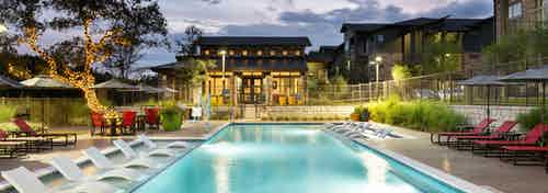 Exterior evening view of AMLI Covered Bridge pool with lounge seating and shaded poolside dining