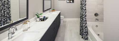 AMLI Addison bathroom with dark wood double vanity sink and garden tub with black and white curtains and pale grey tile floor