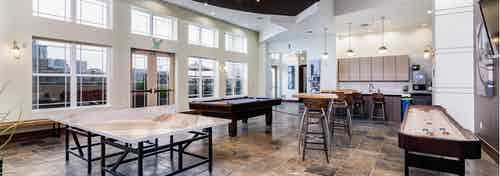 View of the clubroom at AMLI Park Avenue with a shuffle board table and ping pong table and a television and kitchen area