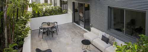 Daytime view of AMLI Midtown Miami apartment patio with table and chairs and other seating surrounded by lush landscaping