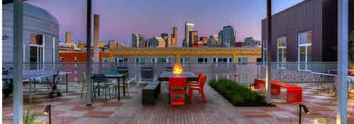AMLI South Lake Union Rooftop deck view of downtown Seattle with fire pit seating floor lighting and lush landscaping