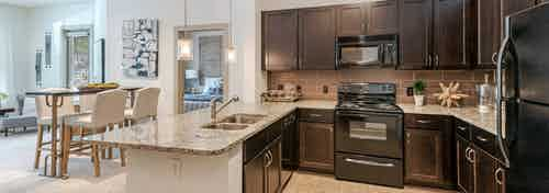 AMLI Parkside apartment spacious kitchen with light tile and dark cabinetry and black appliances with peek into living room