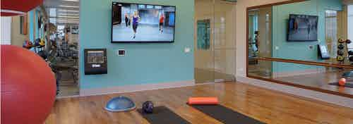 Yoga studio at AMLI River North with a flat screen TV showing an instruction video and two yoga mats laying on the floor
