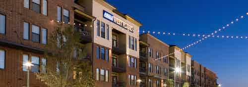 Exterior of AMLI West Plano apartment community at dusk with trees and string lights in front of the building facade