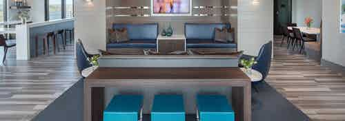 AMLI 3464 clubroom dark wood table in front of blue booth seats and a long white counter with barstools in the background