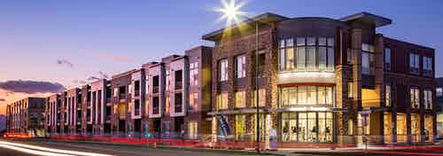 Exterior dusk rendering of AMLI Littleton Village apartment building's brick facade and entrance with lit monument sign