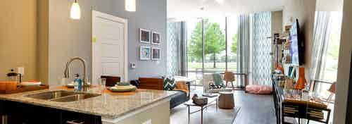 Interior of AMLI at Mueller living room with dark floors and floor to ceiling windows with colorful decor and light walls