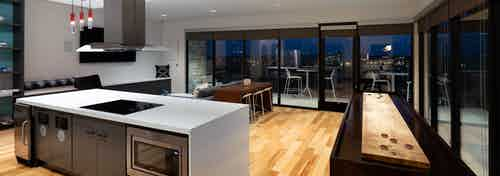 Clubroom at AMLI on Aldrich with floor to ceiling windows showing nighttime view with light wood floors and spacious kitchen