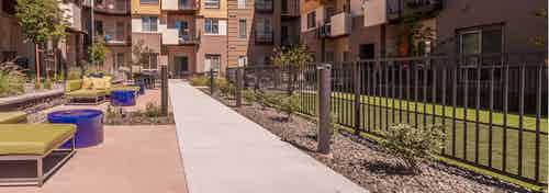 Exterior view of a courtyard area at AMLI Cherry Creek apartments with cement path and multiple seating and view of dog park
