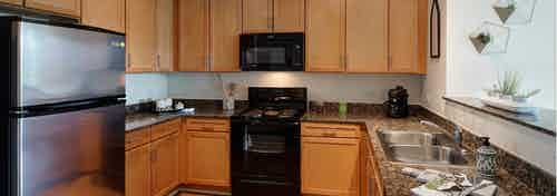 View of a spacious AMLI 900 apartment kitchen with maple cabinets and granite countertops paired with black appliances