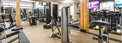 Interior of the fitness center at AMLI Wallingford with treadmills cycle bikes free weights and workout machines