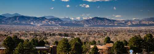 Daytime aerial view above AMLI Littleton Village apartments with the Rocky Mountains from afar, blue sky and lush greenery