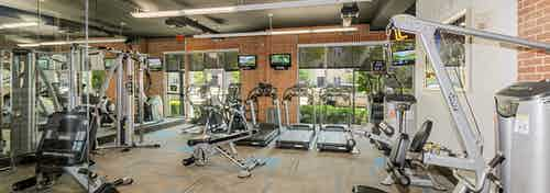 Fitness center at AMLI Las Colinas apartments with cardio and weight machines against a red brick wall with mounted TVs
