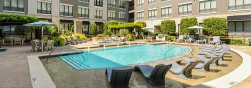 Large courtyard pool at AMLI Las Colinas apartments with in pool lounges and surrounding seating and lush landscaping