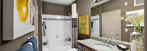 AMLI North Point bathroom with brown walls and white and yellow decor with a large vanity and white tiled bathtub