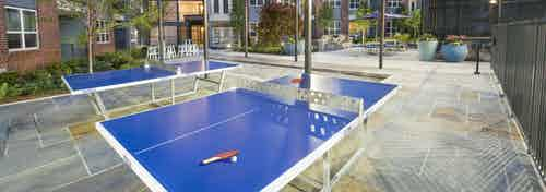 Evening view of ping pong area at AMLI Decatur with blue ping pong tables and hanging lights with seating areas in the back