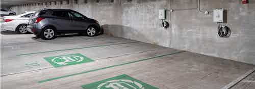 Interior of parking garage at AMLI Deerfield with electric car charging stations and gray and white cars in adjacent spaces