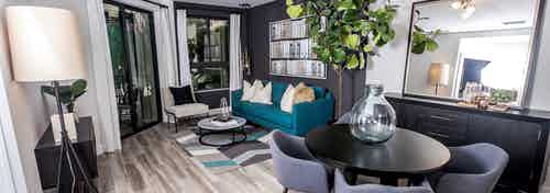 Living area at AMLI Joya apartments with contemporary decor, teal sofa with accent pillows and dining table with chairs