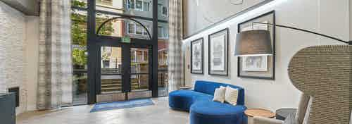 Interior view of AMLI Bellevue Park apartments lobby with two story window over door and blue couch with artwork hanging above
