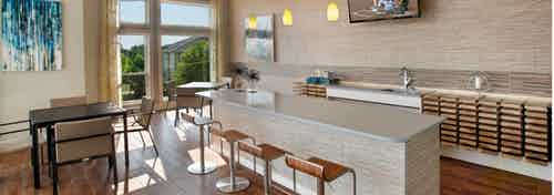 Interior view of sky lounge at AMLI Piedmont Heights apartment building with various seating areas with bar counter and TV