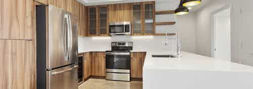 Interior view of spacious kitchen at AMLI on 2nd with stainless steel appliances and smooth white countertops