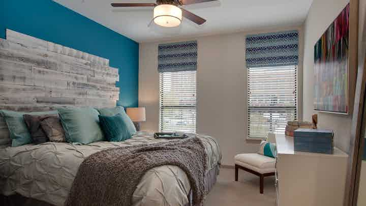 AMLI Ponce Park apartment bedroom with cream walls and carpet flooring with large windows for natural sunlight