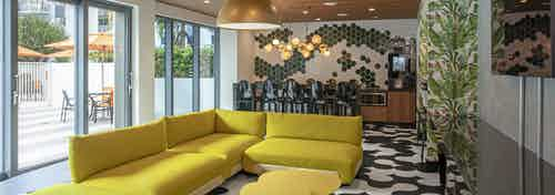 Lounge at AMLI Midtown Miami apartments with yellow modern furniture and black and white tile floor and wall of windows