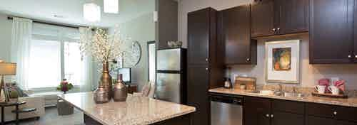 AMLI 5350 island kitchen with dark wood cabinets and granite countertops with peek into living area and window in background
