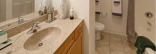 View of an AMLI 900 bathroom featuring modern maple cabinets paired with a light tan colored countertop and tile flooring