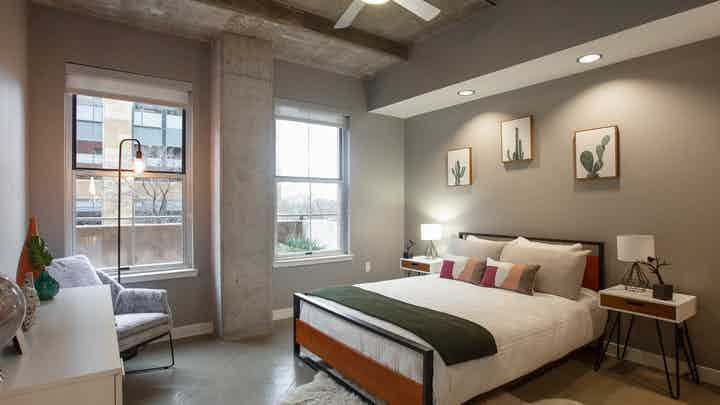 AMLI Downtown bedroom with grey walls and a comfy white bed in front of two large windows with a bright daytime view