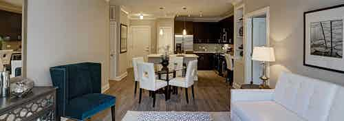 Interior view of AMLI Deerfield apartment community living room into dining room and kitchen with custom crown molding