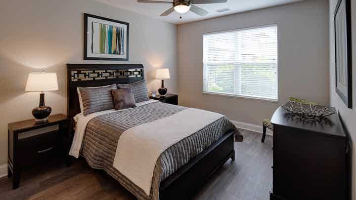 Interior of AMLI Deerfield apartment bedroom with ceiling fan and window furnished with bed and two nightstands and dresser