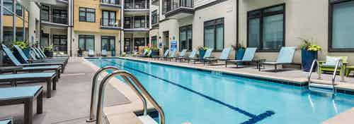 Exterior close up of swimming pool water at AMLI 5350 surrounded by blue lounge chairs and apartment building facade