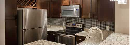 Interior of AMLI Memorial Heights apartment kitchen with dark wood cabinets, tile backsplash and stainless steel appliances