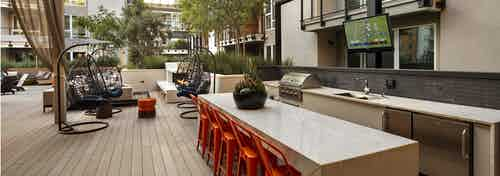 Entertaining grilling station with bar height quartz serving counter, chairs and TV at AMLI Marina Del Rey outdoor lanai