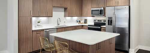 Interior of island kitchen at AMLI Addison with light wood cabinets and white countertops with stainless steel appliances