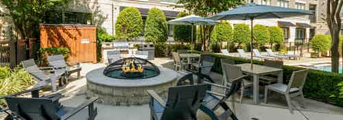 AMLI Las Colinas poolside stone circular fire pit encircled by 9 gray Adirondack chairs and nearby grill and tables and chairs