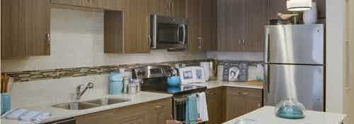 AMLI Ponce Park apartment kitchen showcasing stainless steel appliances nested in dark cabinets with white tile backsplash