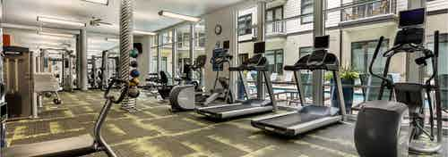 AMLI 5350 fitness center with treadmills facing tall windows and a variety of other exercise machines in the background