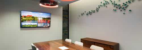 Interior view of conference room at AMLI on Aldrich with large wooden desk and a flat screen TV hanging on neutral wall
