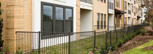 Daytime exterior view of fenced yards with green grass and landscaping outside AMLI Campion Trail apartment building