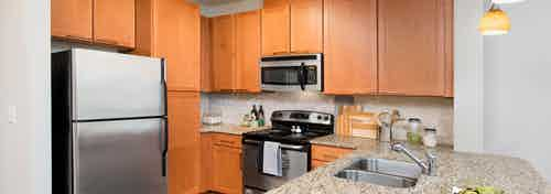 AMLI North Point kitchen with medium colored wood cabinets and stainless steel appliances with spacious granite countertops