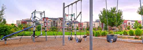 A playground in the surrounding area of AMLI Arista apartments with swings and a jungle gym and landscaped with wood chips